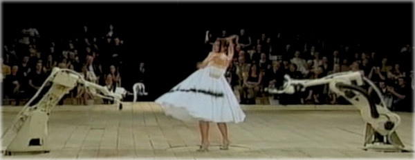 Model in a white gown is closed in upon by robotic spray guns which seem to maul her with black and yellow paint as she spins deliriously. This was created by Lee Alexander McQueen.